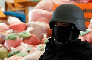 A policeman stands guard near bags of methamphetamine pills during the 39th Destruction of Confiscated Narcotics in Ayutthaya province, nearly 80 km (50 miles) north of Bangkok, June 24, 2011. AAbout 5,844 kg (12,884 lbs) of drugs, among them methamphetamines, marijuana, heroin and opium worth more than 7,400 million baht ($242 million) were destroyed to commemorate Drugs Free Day on June 26, according to the Thai Public Health Ministry. REUTERS/Sukree Sukplang (THAILAND - Tags: CRIME LAW SOCIETY) - RTR2O11F