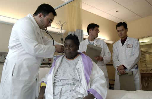 A doctor examines a patient, while other doctors look on