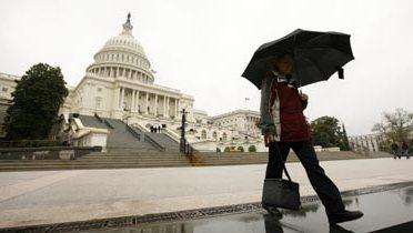 A person holding an umbrella walking near the U.S. Capitol building.