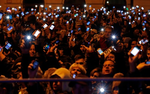 Protesters raise their smartphones with screens lit