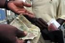 Reuters/Thierry Gouegnon - People exchange money in Abidjan, December 31, 2004.