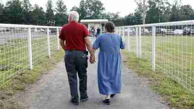 Two elderly individuals walk along a path in a rural area