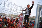Reuters/Umit Bektas - Refugee youths gesture from behind a fence as German Chancellor Angela Merkel, Turkish Prime Minister Ahmet Davutoglu, EU Council President Donald Tusk and European Commission Vice-President Frans Timmermans (all not pictured) arrive at Nizip refugee camp near Gaziantep, Turkey, April 23, 2016