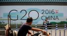 People cycle past a billboard for the upcoming G20 summit in Hangzhou, Zhejiang province, China, July 29, 2016. Picture taken July 29, 2016. REUTERS/Aly Song - RTSL4WN