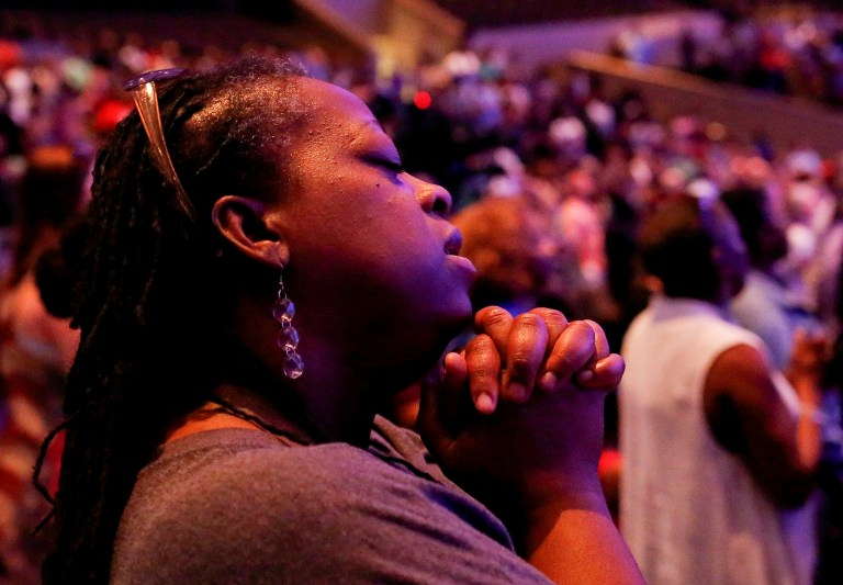 A woman holds her hands during a prayer service at the Concord Baptist Church, one day after a lone gunman ambushed and killed five police officers at a protest decrying police shootings of black men, in Dallas, Texas, U.S., July 8, 2016. REUTERS/Shannon Stapleton TPX IMAGES OF THE DAY - RTSH11E