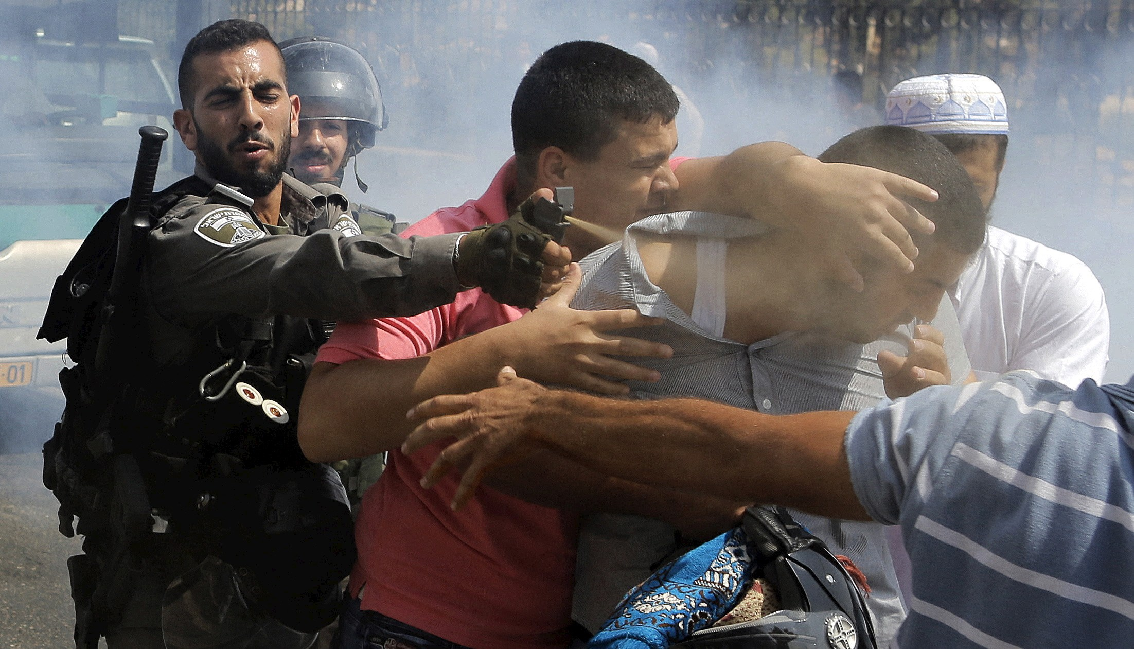 Israeli border policeman uses pepper spray on a Palestinian man during clashes near Arab East Jerusalem