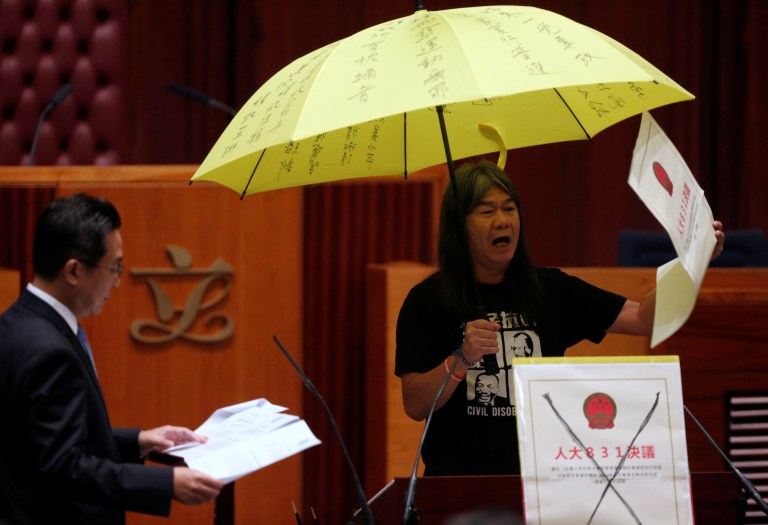 Re-elected lawmaker Leung Kwok-hung holds an umbrella while taking oath at the Legislative Council in Hong Kong, China October 12, 2016. REUTERS/Bobby Yip TPX IMAGES OF THE DAY - RTSRVA6