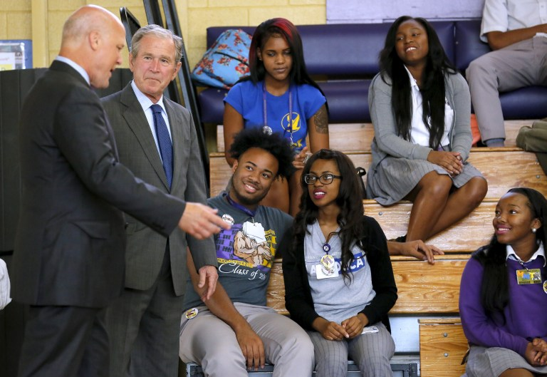 Former U.S. President George W. Bush and New Orleans Mayor Mitch Landrieu (L) talk to students at Warren Easton Charter High School one day before the ten year anniversary of Hurricane Katrina in New Orleans