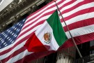 The flag of Mexico changes in front of a large U.S. flag in front of the New York Stock Exchange September 4, 2015. REUTERS/Lucas Jackson - RTX1R4GU