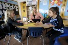 Kyle Schwartz (C), a 3rd grade teacher, works with students Mckylah Lenkiewicz (L) and Juliana Enquist in her classroom at Doull Elementary School in Denver