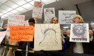 "Dozens of pro-immigration demonstrators cheer and hold signs as international passengers arrive at Dulles International Airport, to protest President Donald Trump's executive order barring visitors, refugees and immigrants from certain countries to the United States, in Chantilly, Virginia, in suburban Washington, U.S., January 29, 2017. The sign in Arabic (L) reads ""Have you been stopped and questioned, we would like to talk to you, to assist with a lawyer"". REUTERS/Mike Theiler - RTSXYQ0"