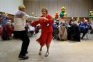 Anita Monk and her neighbour John Everett dance during a Christmas Dinner event for older people.