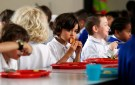 Students eat lunch at Salusbury Primary School in northwest London June 11, 2014. This September, a new government scheme plans to give free meals to all reception, year 1 and 2 students registered in England's state-funded schools. Local media reports that this will amount to saving families about ?400 a year per child. REUTERS/Suzanne Plunkett (BRITAIN - Tags: EDUCATION SOCIETY FOOD) - RTR3T864