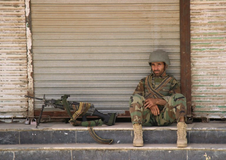 An Afghan National Army (ANA) soldier sits in front of a closed shop in the downtown of Kunduz city, Afghanistan October 3, 2016.REUTERS/Nasir Wakif TPX IMAGES OF THE DAY - RTSQMEJ