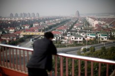 A man watches the Huaxi village, at Jiangsu province December 2, 2010. In China's richest village of Huaxi, a booming market town of 36,000 in the affluent eastern province of Jiangsu, every family has at least one house, two cars and $250,000 in the bank. Officials from elsewhere in China tour Huaxi to find out how this once sleepy village, just 576 residents in the 1950s, is now so rich and why non-local businessmen would donate million-dollar factories to buy the privilege of a local residence permit. Picture taken December 2, 2010. REUTERS/Carlos Barria (CHINA - Tags: POLITICS BUSINESS SOCIETY) - RTXVCES