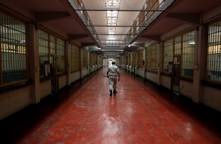 A security guard walks the hall of a prison