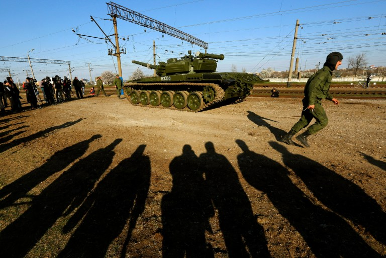 A Russian tank crew member runs in front of his T-72B tank after their arrival in Crimea in the settlement of Gvardeiskoye near the Crimean city of Simferopol March 31, 2014. Russia is withdrawing a motorized infantry battalion from a region near Ukraine's eastern border, the Russian Defence Ministry was quoted as saying by state news agencies on Monday. REUTERS/Yannis Behrakis (UKRAINE - Tags: POLITICS CONFLICT TPX IMAGES OF THE DAY) - RTR3JCY3