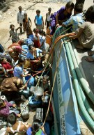People crowd around a water tanker to fill their buckets and pots in the western Indian city of Ahmedabad May 11, 2006. At least 27 people have died in India from scorching weather, officials said on Monday. REUTERS/Amit Dave - RTR1DA14