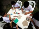 Children paint handmade sheets of paper made from recycled cigarette butts in a school in Votorantim, Sao Paulo, Brazil, March 7, 2017. Picture taken March 7, 2017.  REUTERS/Paulo Whitaker - RTS11ZHQ