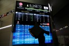 A worker carries a chair as he walks next to an electronic stock board at the Indonesia Stock Exchange in Jakarta, Indonesia February 3, 2017. REUTERS/Beawiharta - RTX2ZFJ7
