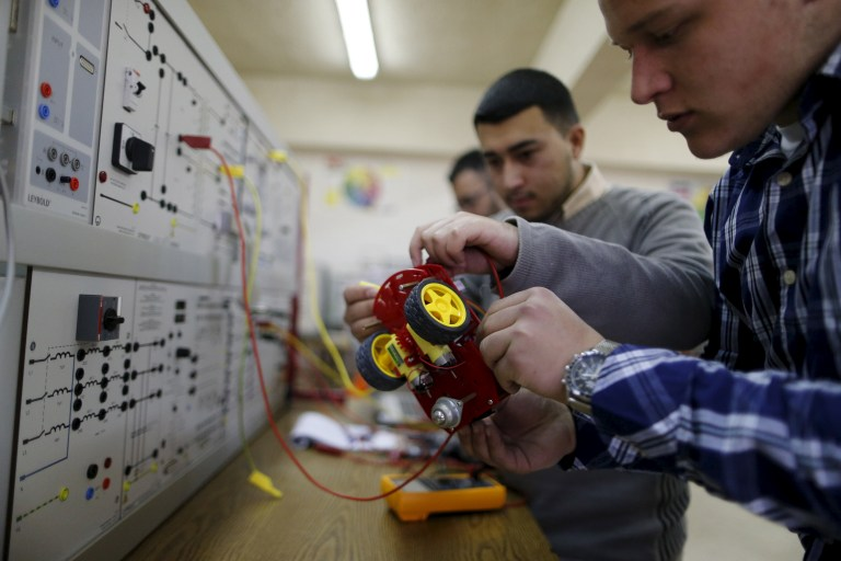 Palestinian students check a small electronic car that they control by an electronic glove they developed, at Birzeit University in the West Bank town of Birzeit January 21, 2016. Three Palestinian student developed the electronic glove that can be used to control several devices, including laptops and robots, as part of their graduation project. REUTERS/Ammar Awad