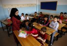 "A Syrian refugee teacher distributes books to her refugee students in their classroom at Fatih Sultan Mehmet School in Karapurcek district of Ankara, Turkey, September 28, 2015. Out of 640,000 Syrian children in Turkey, 400,000 are not at school, a Turkish official told Reuters on Friday, warning that those who miss out are likely to be exploited by ""gangs and criminals"". Educating the children among more than 2.2 million Syrian refugees in Turkey - most of whom live outside purpose-built camps - is seen as a critical part of the humanitarian response to the four-and-a-half-year-old conflict. Picture taken September 28, 2015. REUTERS/Umit Bektas  - RTS2SL7"
