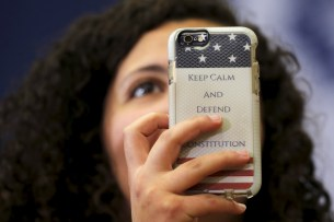 "An audience member holds up a phone with a case reading ""Keep Calm and Defend the Constitution"" during a ""Get Out to Caucus"" rally with U.S. Democratic presidential candidate Hillary Clinton in Cedar Rapids, Iowa"