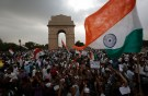 Supporters of veteran Indian social activist Hazare wave India's national flags at the India Gate during a hunger strike by Hazare and his team members in New Delhi
