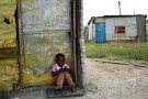 A child sits outside a locked shack in Nkaneng township, Marikana's informal settlement, in Rustenburg