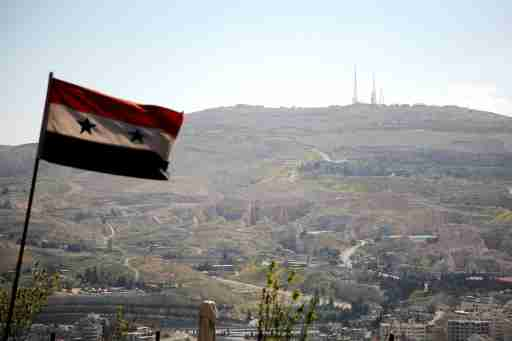 A Syrian national flag flutters as Qasioun mountain is seen in the background from Damascus, Syria April 7, 2017. REUTERS/Omar Sanadiki - RTX34I6K