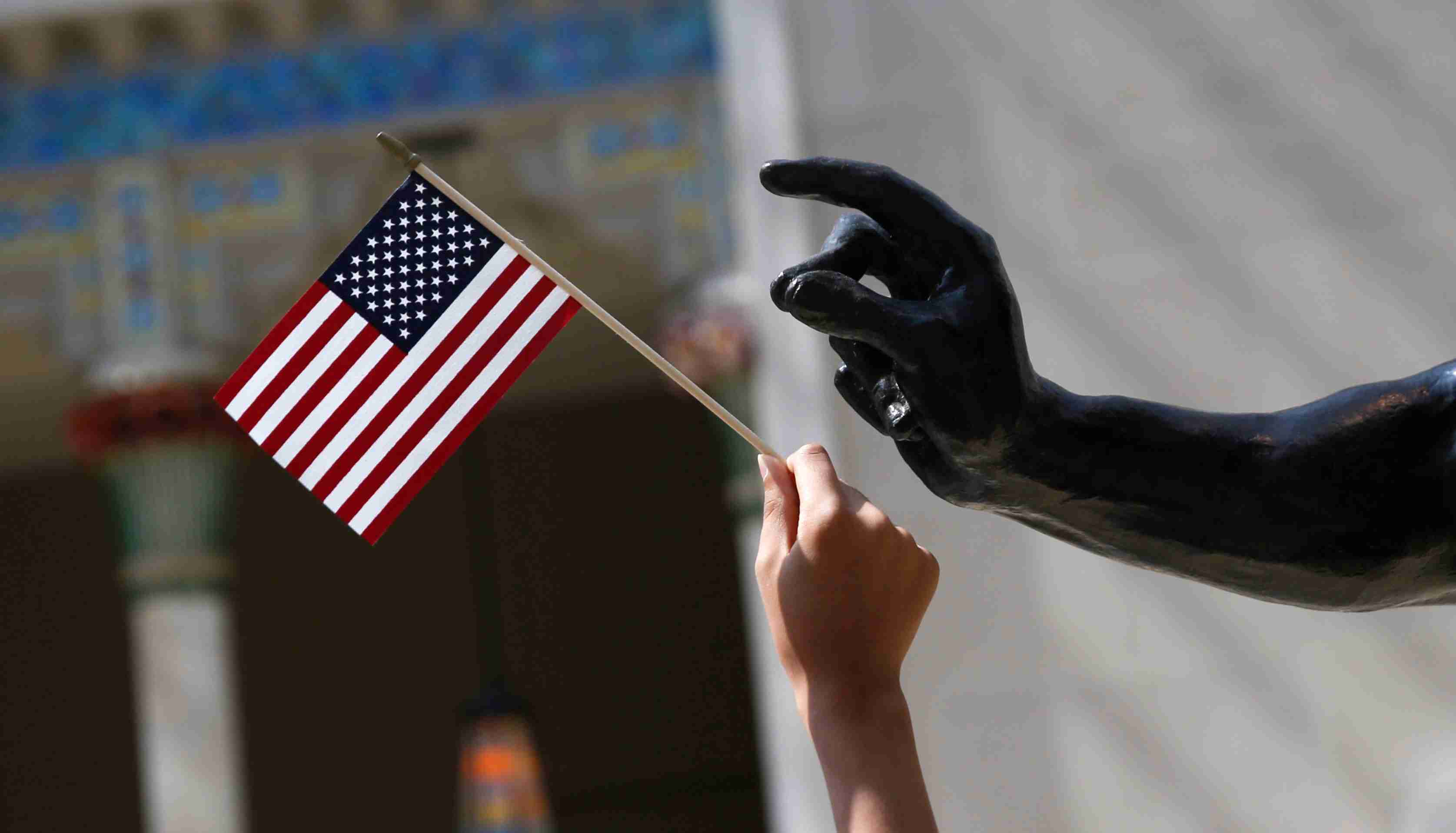 A girl holds a U.S. flag next to a sculpture after a naturalization ceremony at The Metropolitan Museum of Art in New York July 22, 2014. Seventy-five people from 42 countries became American citizens at an event held by U.S. Citizenship and Immigration Services (USCIS) at the Museum.