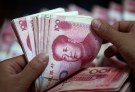 A bank clerk counts Chinese yuan