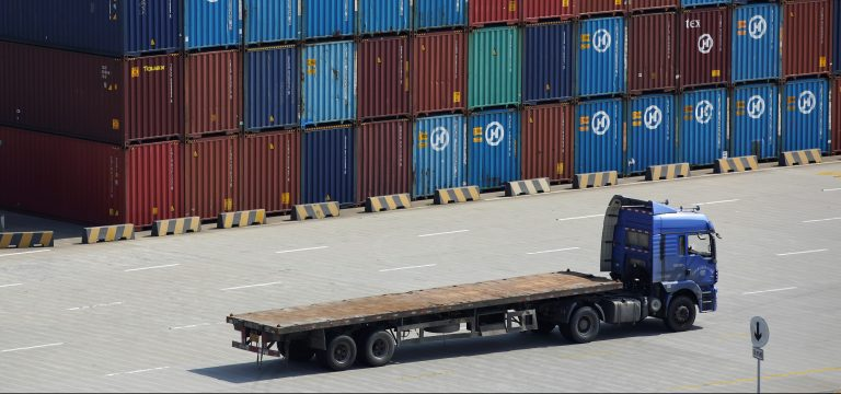A truck drives past container boxes at the Yangshan Deep Water Port, part of the Shanghai Free Trade Zone, in Shanghai, China, September 24, 2016. Picture taken September 24, 2016. REUTERS/Aly Song - RTSPFVH