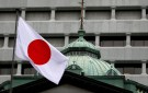 A Japanese flag flutters atop the Bank of Japan building.