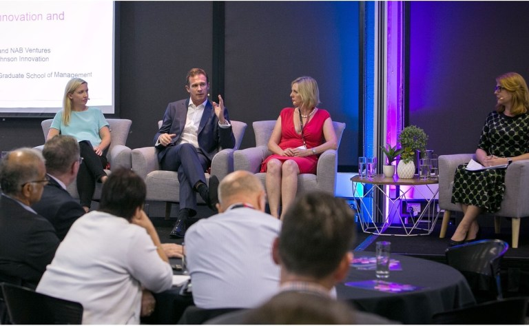 3 women and one man sit in a panel on a stage in the front of a room at the Macquarie Park innovation district in Sydney, Australia in February 2017 discussing innovation districts.