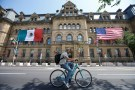 The Mexican and U.S. flags hang from the Langevin Block in advance of Wednesday's North American Leaders' Summit as a cyclist passes by in Ottawa, Ontario, Canada, June 27, 2016. REUTERS/Chris Wattie - RTX2IK28