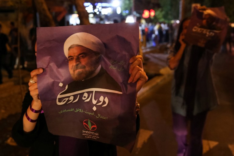 A supporter of Iranian president Hassan Rouhani holds his poster as she celebrates his victory in the presidential election, in Tehran, Iran, May 20, 2017. TIMA via REUTERS ATTENTION EDITORS - THIS IMAGE WAS PROVIDED BY A THIRD PARTY. FOR EDITORIAL USE ONLY. - RTX36R4M