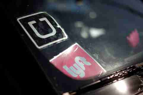 The corporate logos of Uber and Lyft are displayed on a driver's windshield.