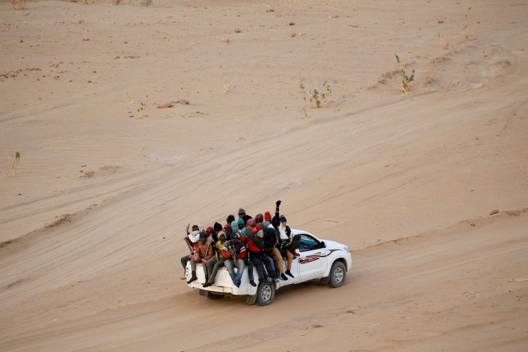 Migrants crossing the Sahara desert into Libya ride on the back of a pickup truck outside Agadez, Niger, May 9, 2016. Picture taken May 9, 2016. To match Analysis EUROPE-MIGRANTS/AFRICA REUTERS/Joe Penney - RTSS2Q8