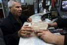 A man (L) changes Iraqi dinars to U.S. dollars at a currency exchange shop in Baghdad December 21, 2015. REUTERS/Khalid al Mousily   - RTX1ZM94