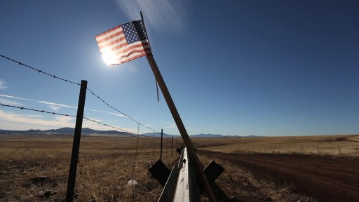 fencing and a U.S. flag along the U.S.-Mexico border