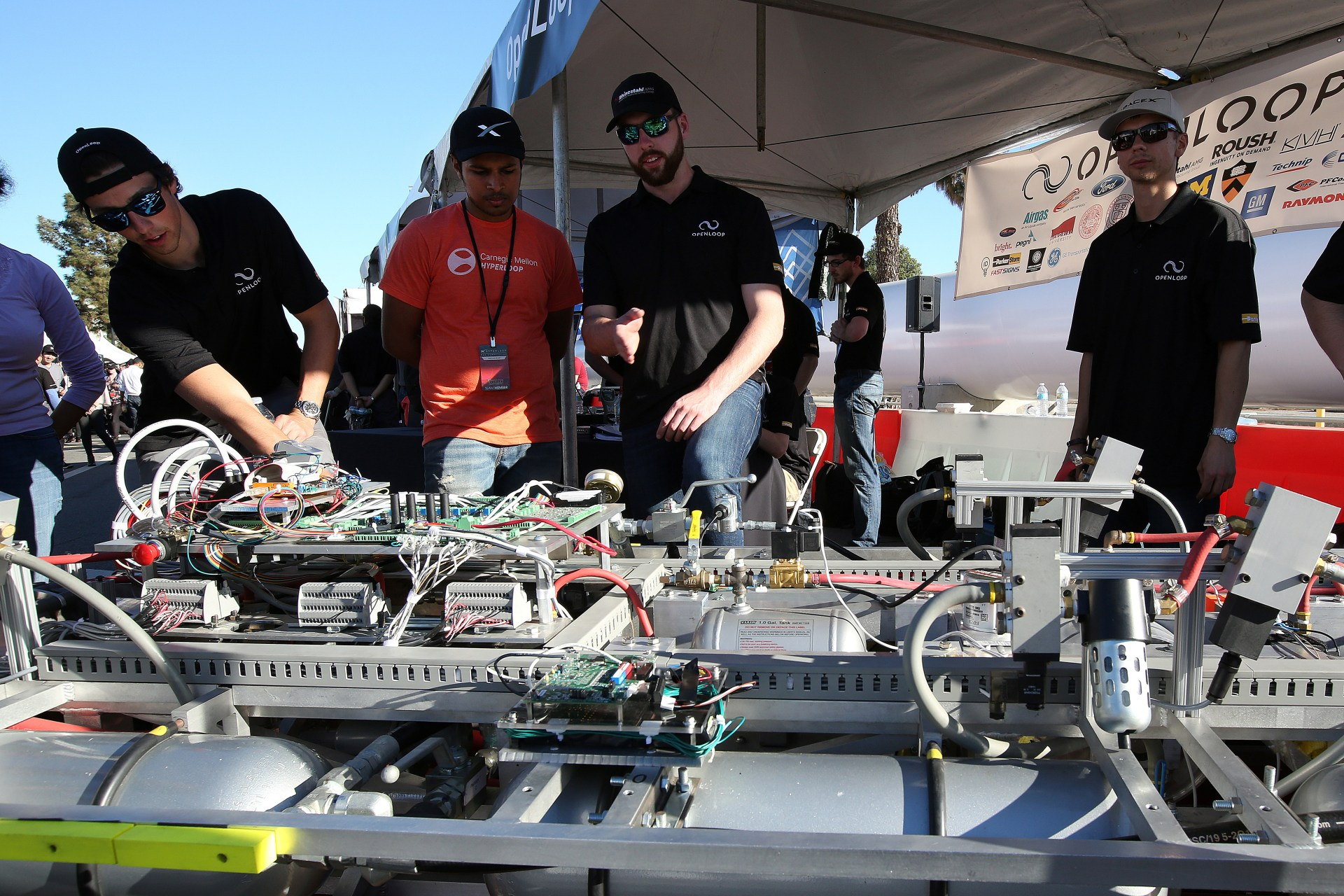 Team members from Openloop, a six school alliance including Northeastern, Memorial University, Princeton, Cornell, Harvey Mudd College and the University of Michigan look at the electronics of their pod in their booth during the SpaceX Hyperloop Pod Competition in Hawthorne, Los Angeles, California, U.S., January 29, 2017. REUTERS/Monica Almeida - RTSY02S