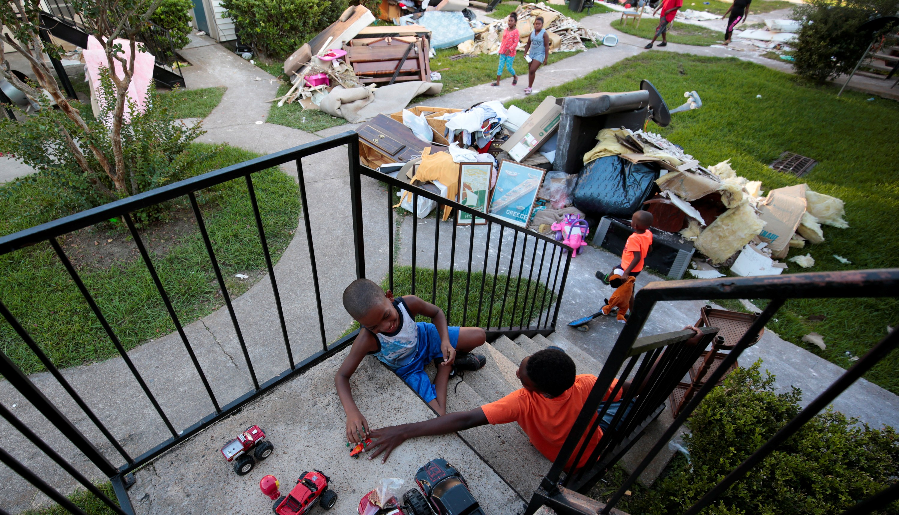 From left, Darius Smith, 9,  Kameron Smith, 4, and Deandre Green, 10, play with toys that they found in the piles of destroyed property at Crofton Place Apartments in the aftermath of Hurricane Harvey in Houston, Texas, U.S. September 8, 2017. The children's apartment was destroyed by the flood waters. Picture taken September 8, 2017. REUTERS/Chris Aluka Berry - RC18FC12F660