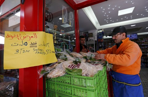 """An Arabic sign that reads: """"3 Syrian style bread 5 lira"""" is seen at a market in Istanbul, Turkey February 17, 2016. Turkey's 2.6 million Syrian refugees may be straining the housing and jobs systems, but they're also fuelling economic growth. The world's largest refugee population has had a positive impact on Turkish output, economists and government officials say. It may be partly responsible for an unexpected rise in third-quarter growth and stronger forecasts for 2016 output. Picture taken February 17, 2016. REUTERS/Murad Sezer  - GF10000315754"""