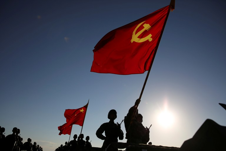 Soldiers carry a Chinese Communist Party flag and Chinese national flags before the military parade to commemorate the 90th anniversary of the foundation of China's People's Liberation Army (PLA) at Zhurihe military base in Inner Mongolia Autonomous Region