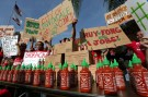 Supporters of Sriracha hot sauce attend a rally at Irwindale City Hall, in Irwindale, California April 23, 2014. The Southern California makers of the popular Sriracha brand of hot sauce faced another potential showdown on Wednesday with the city of Irwindale over a peppery smell emitted from the company's chili-processing factory in town. Irwindale filed a lawsuit against Huy Fong Foods last October saying the smell of peppers being crushed at the plant was causing headaches and irritating the eyes and throats of nearby residents, forcing some to remain indoors. The city council was expected to announce their decision on a resolution formally declaring Huy Fong factory a public nuisance in Irwindale in Wednesday night's council meeting, but the announcement was postponed. REUTERS/Jonathan Alcorn (UNITED STATES - Tags: POLITICS CIVIL UNREST FOOD BUSINESS) - GM1EA4O0XS501