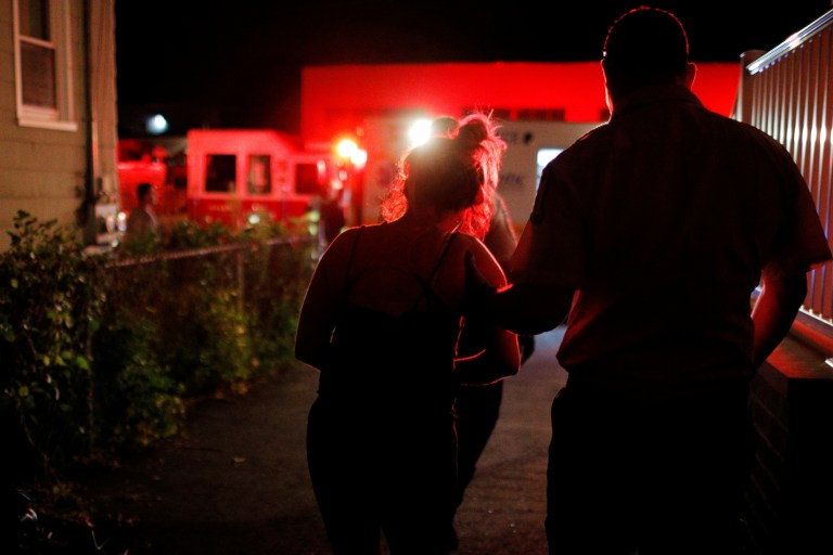 """A Cataldo Ambulance medic escorts a 39-year-old woman to an ambulance after she was revived from an opioid overdose in a home in the Boston suburb of Salem, Massachusetts, U.S., August 15, 2017. The woman was revived with 4mg of naloxone. REUTERS/Brian Snyder SEARCH """"SNYDER OPIOIDS"""" FOR THIS STORY. SEARCH """"WIDER IMAGE"""" FOR ALL STORIES. - RC1F62534430"""