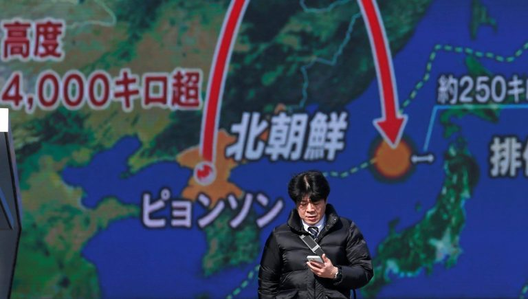 A man walks past a street monitor showing a news report about North Korea's missile launch, in Tokyo, Japan, November 29, 2017. REUTERS/Toru Hanai - RC14E67BAE70