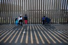 People hold conversations through the U.S. Mexico border wall at Border Field State Park in San Diego, California, U.S., November 18, 2017.      REUTERS/Mike Blake - RC1318FF90D0