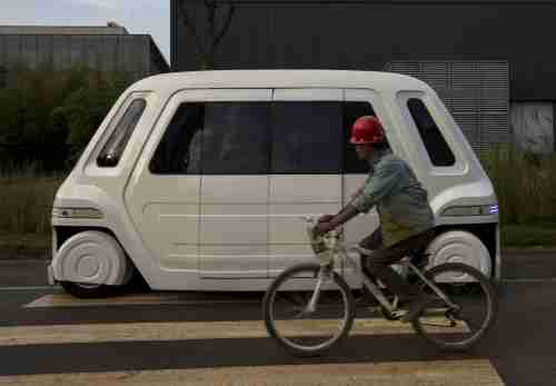 A worker rides a bike past a driverless vehicle at Vanke's Building Research Centre testing area in Dongguan